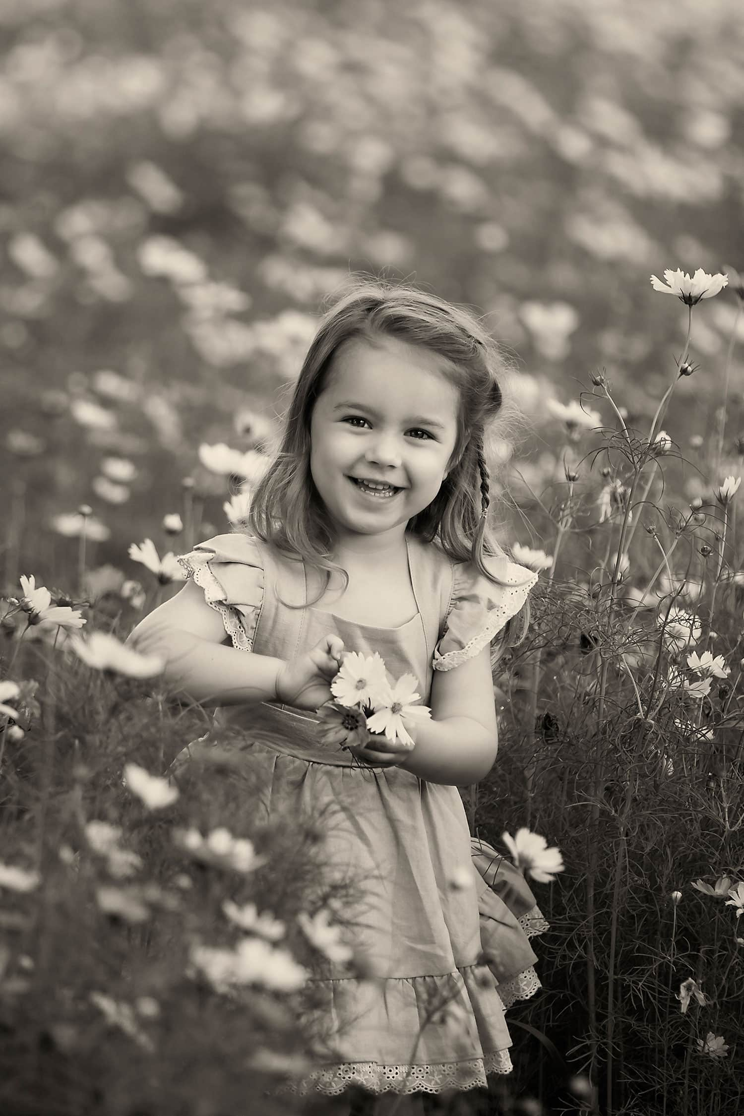 Black and white photo of girl in wildflowers by Annie Whitaker Photography