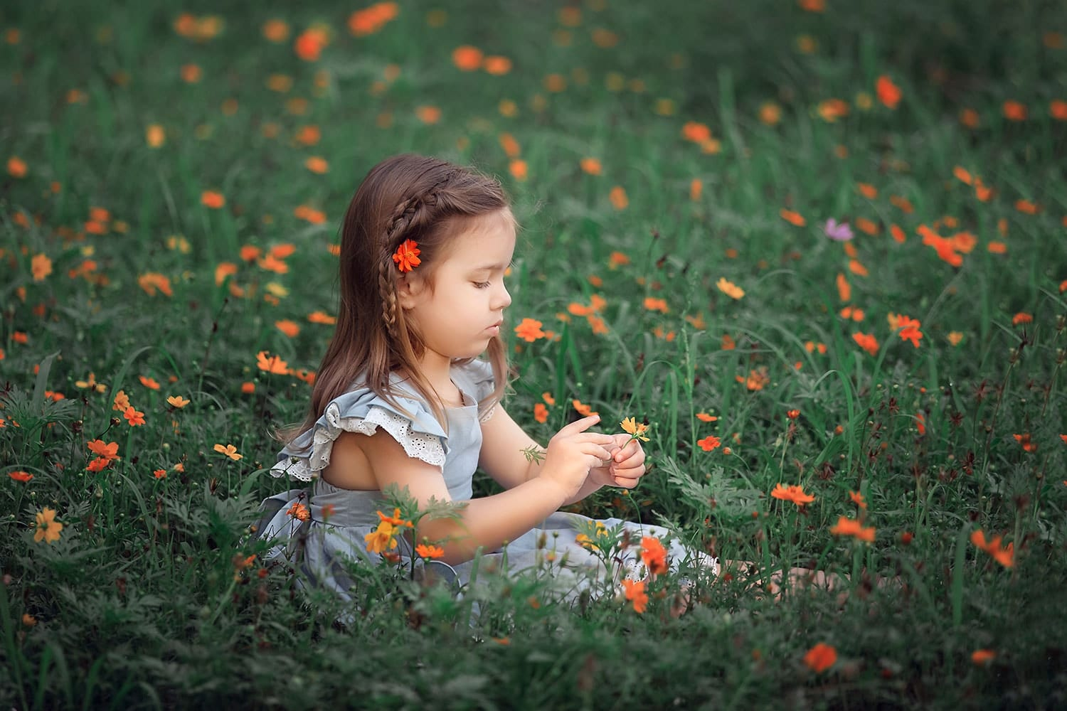 Toddler girl in orange flowers by Annie Whitaker Photography