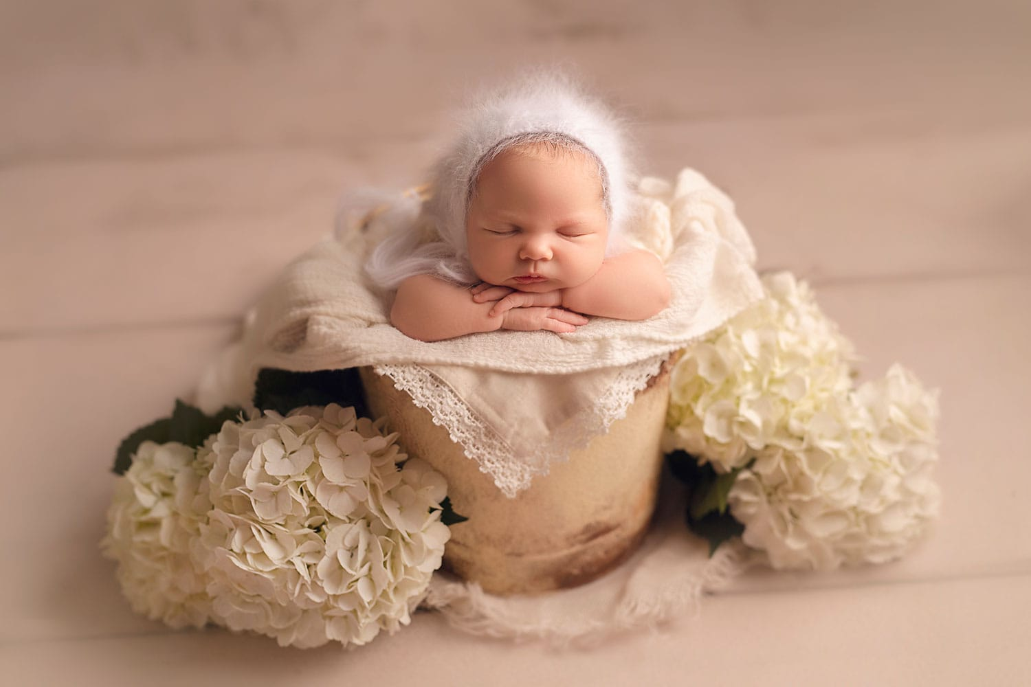 Newborn baby in bucket surrounded by flowers by Annie Whitaker Photgraphy