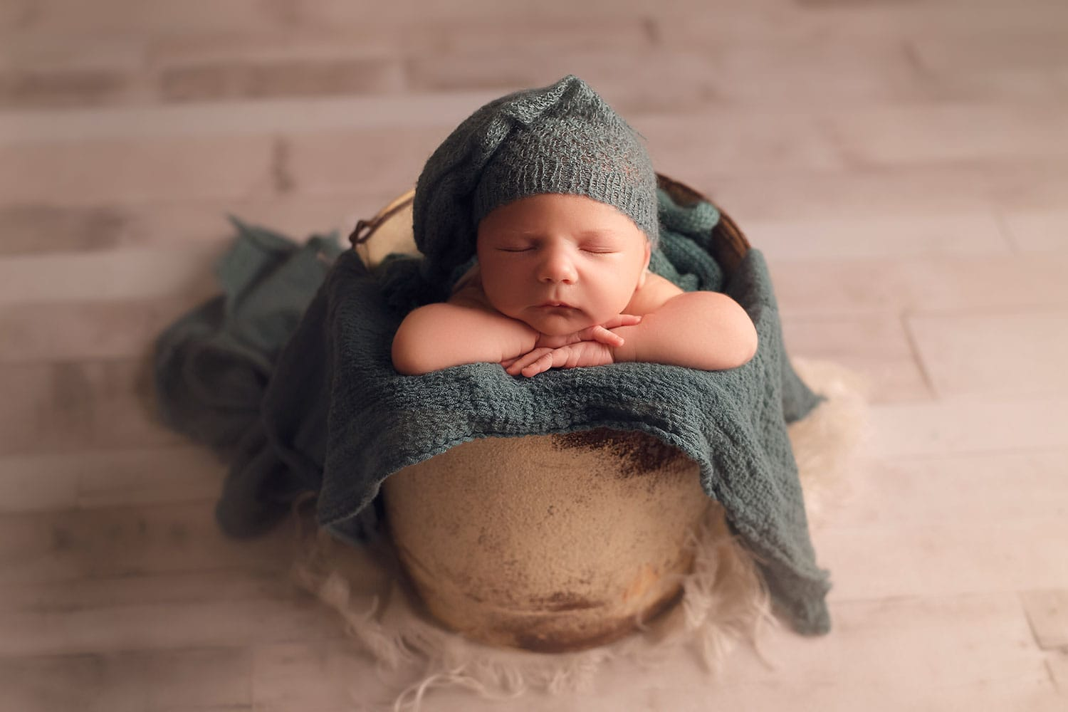 Newborn boy in white bucket with teal wrap and sleepy hat by Annie Whitaker Photography