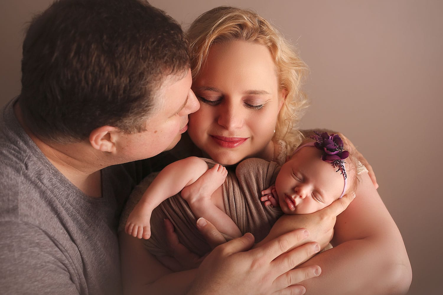 dad kissing mom with newborn by Annie Whitaker Photography