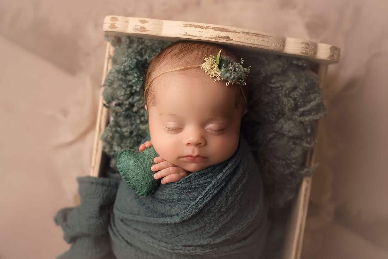 Newborn girl holding teal heart by Annie Whitaker Photography