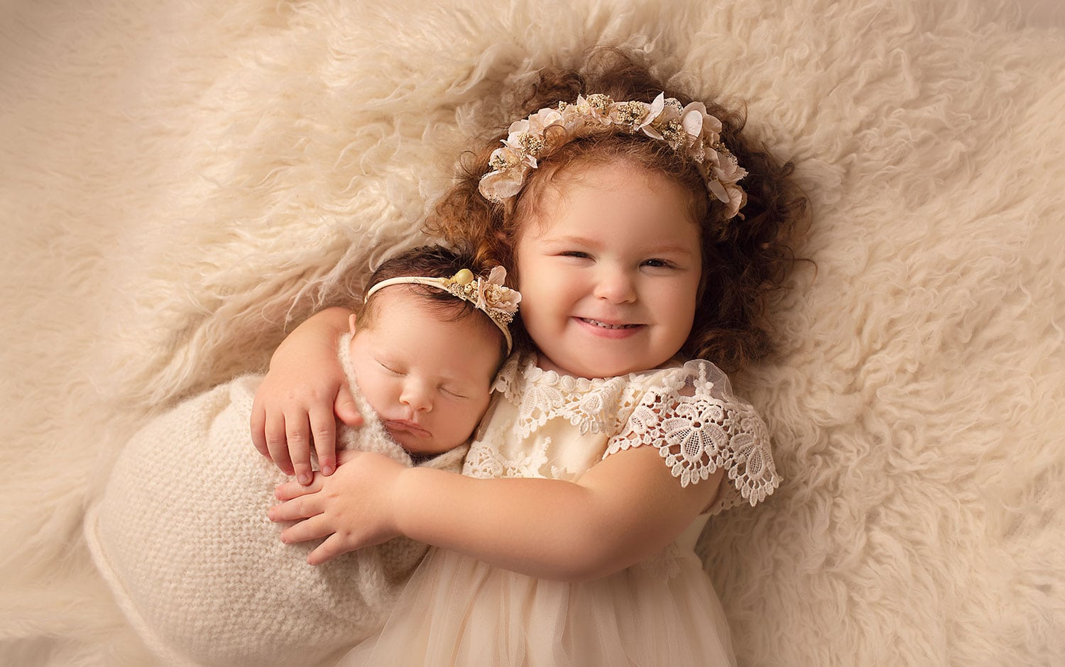 2 year old girl holding baby sister by Annie Whitaker PHotography