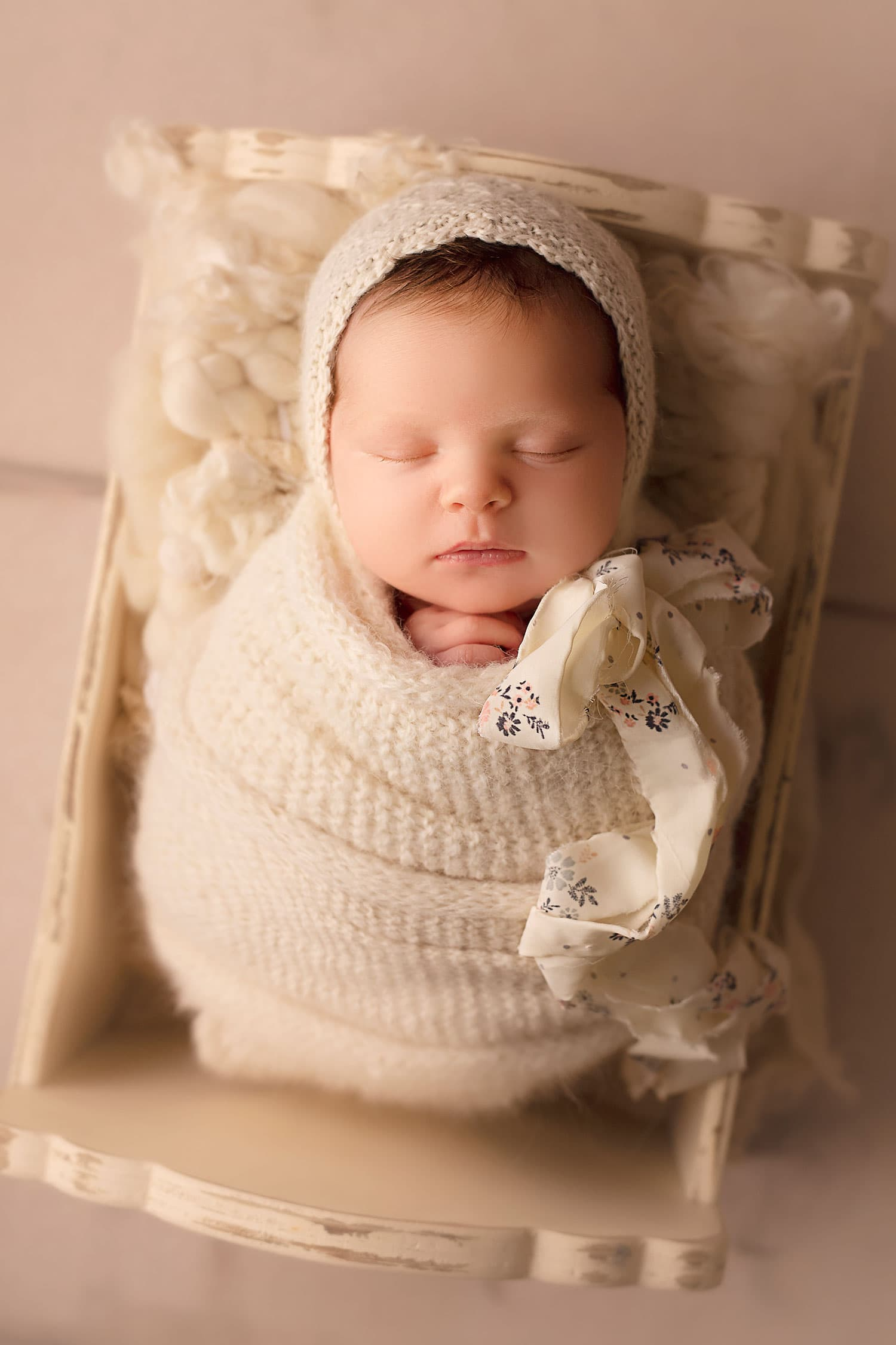 newborn baby in white bonnet by Annie Whitaker Photography