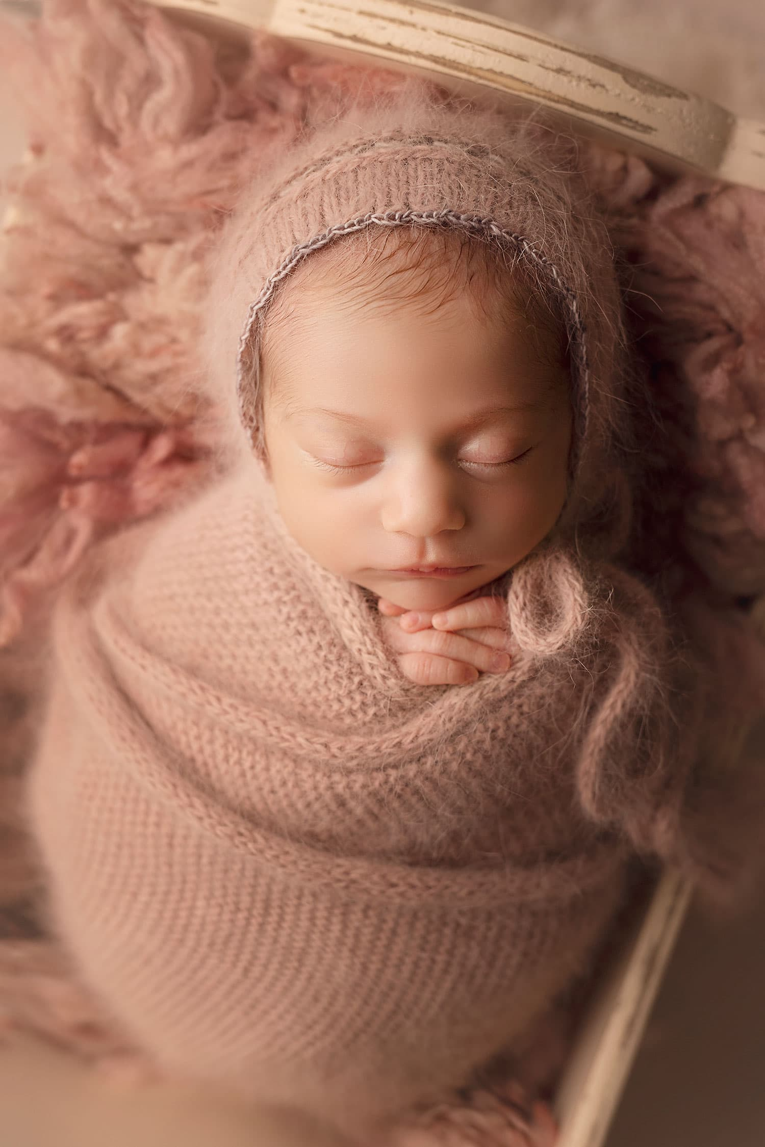 baby girl in pink wrap and bonnet by Annie Whitaker Photography