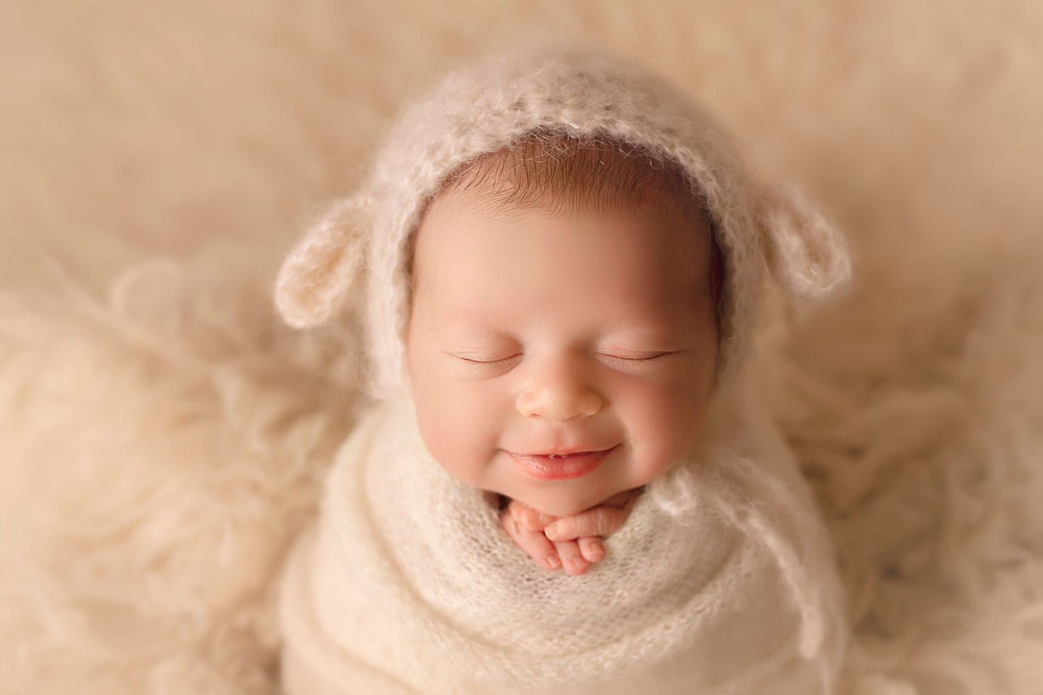 newborn baby smiling in lamb bonnet by Annie Whitaker Photography