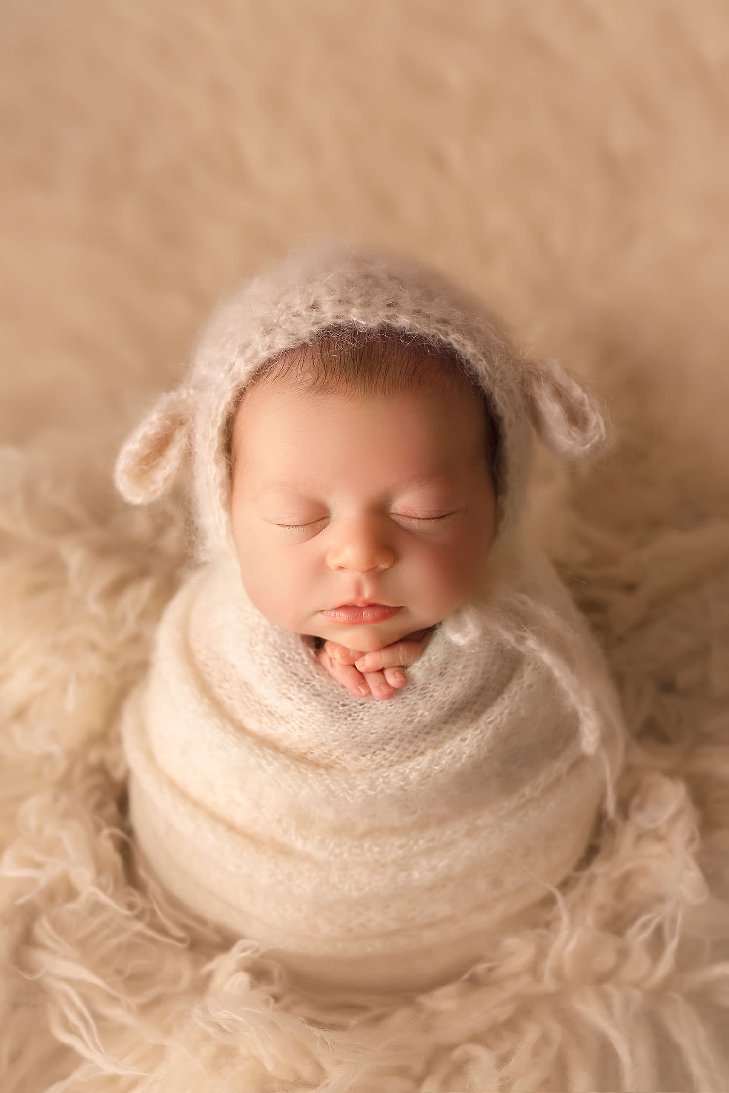 Newborn baby in lamb bonnet by Annie Whitaker Photography
