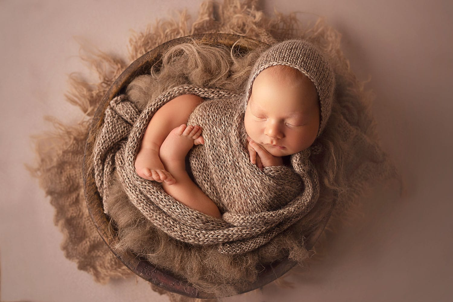 newborn boy in brown wrap and bonnet in bowl by Annie Whitaker Photography
