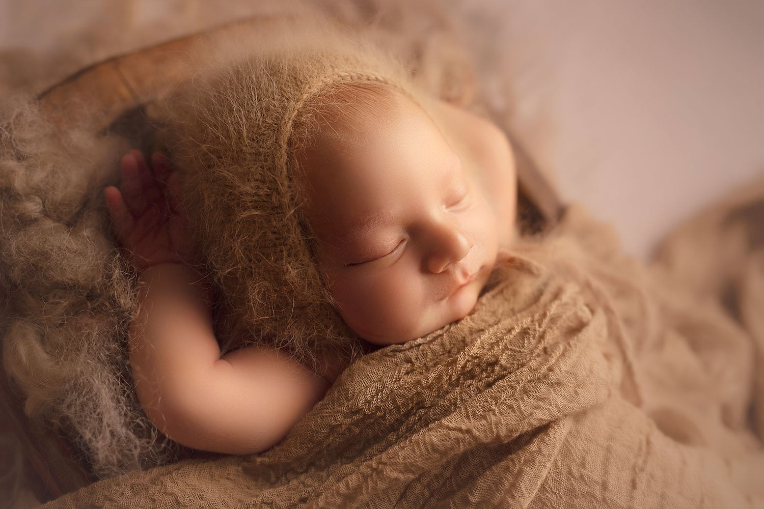 sleeping newborn in camel colored bonnet by Annie Whitaker Photography