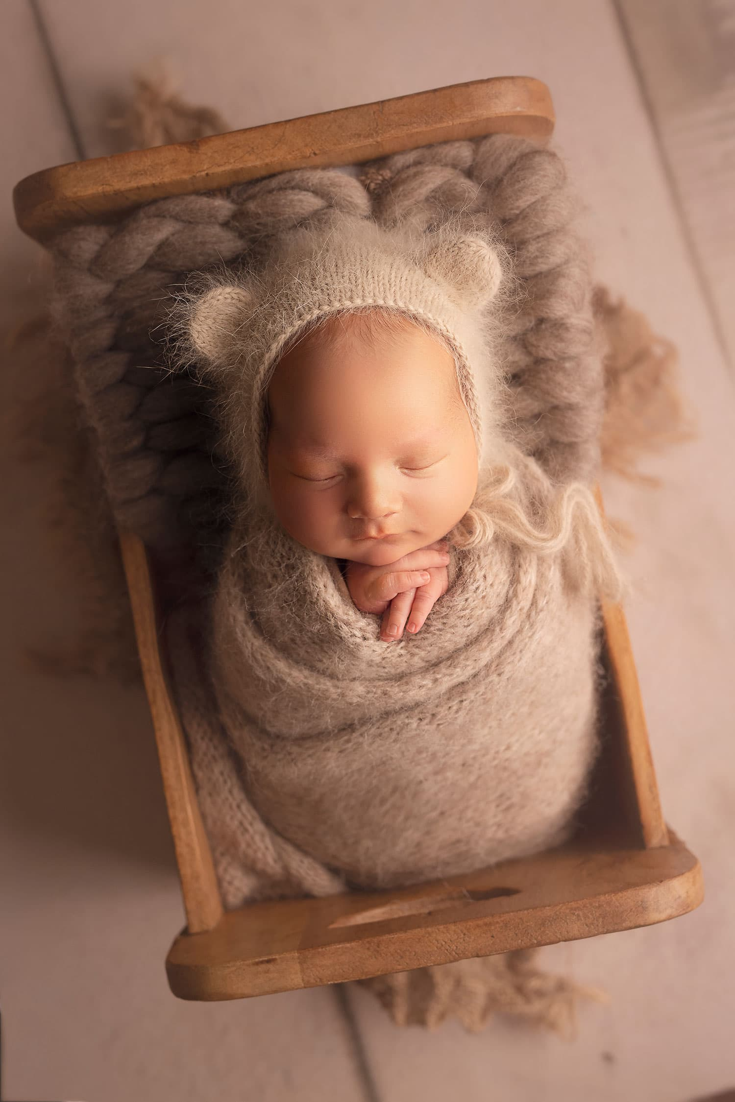 newborn baby boy in bear bonnet in tiny bed by annie Whitaker Photography
