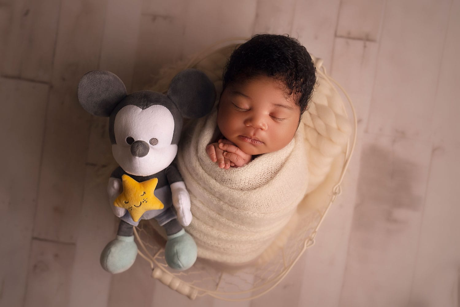 newborn baby with mickey mouse toy by Annie Whitaker Photography