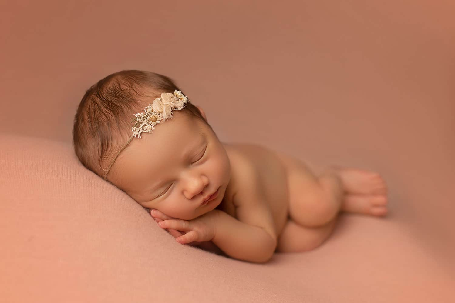 newborn girl on peach back drop by annie Whitaker Photography