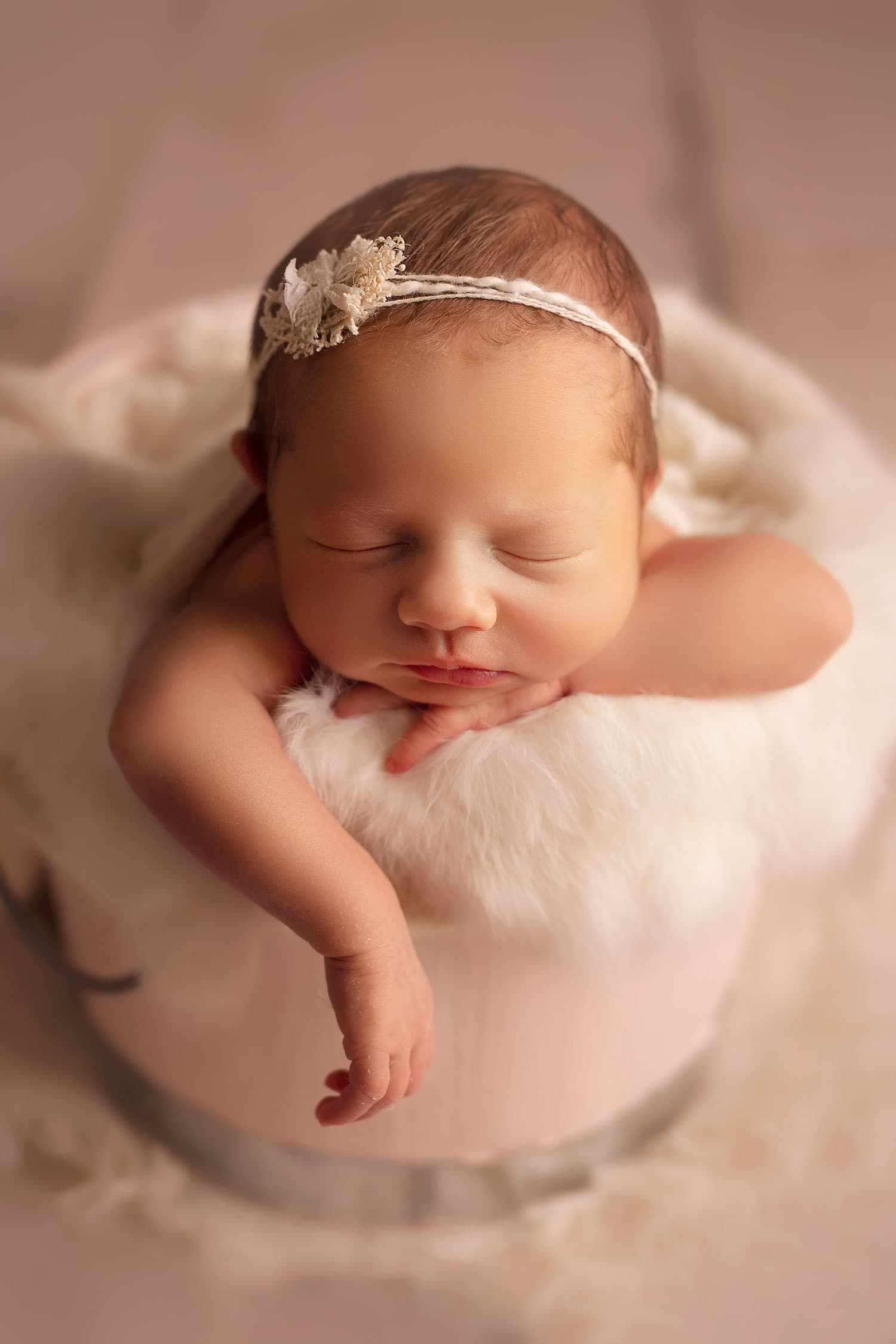 tiny newborn girl in pink bucket by Annie Whitaker Photography