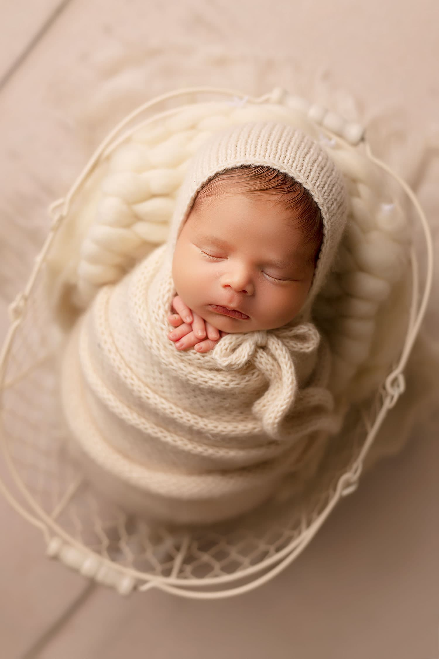 Newborn boy in all cream basket by Annie Whitaker Photography