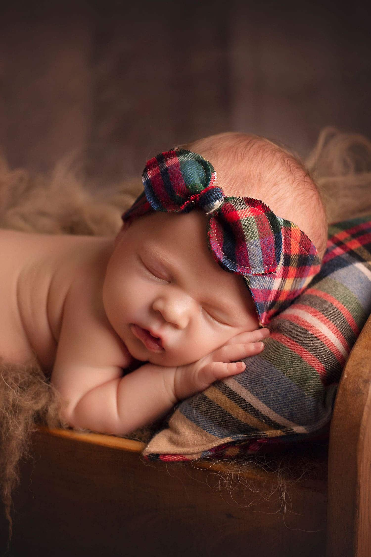 Baby girl in tiny bed by Annie Whitaker Photography