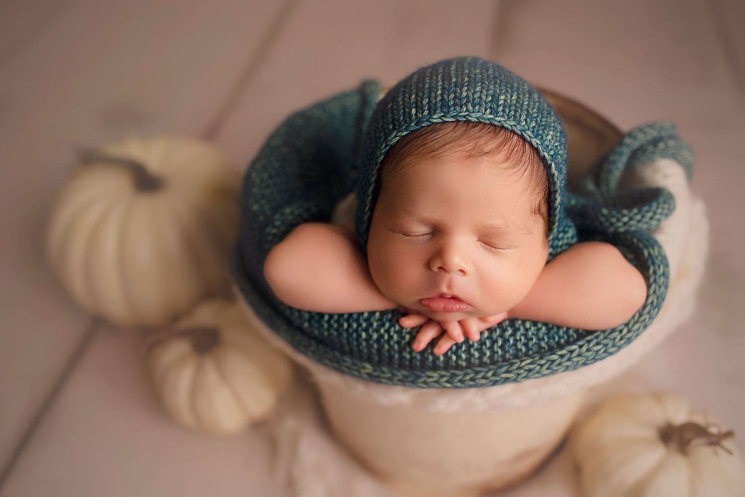 Newborn boy in bucket with pumpkins by Annie Whitaker Photography