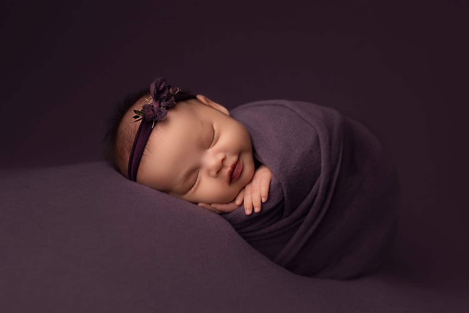 Newborn baby on plum backdrop by Annie Whitaker Photography