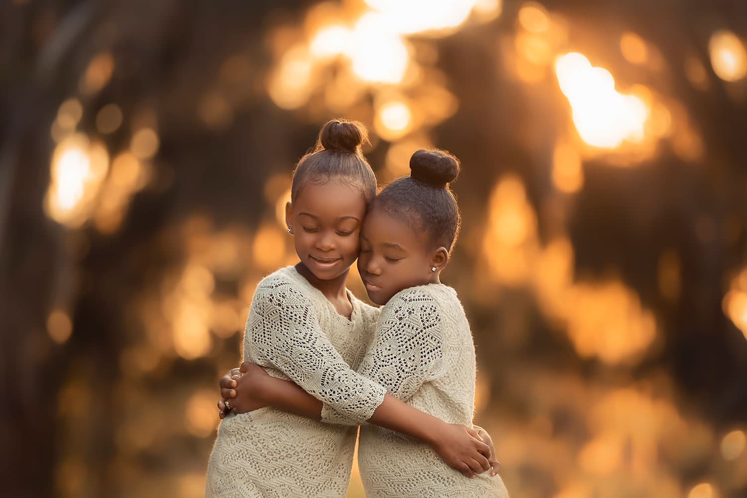 Two sisters hugging at sunset by Annie Whitaker Photography
