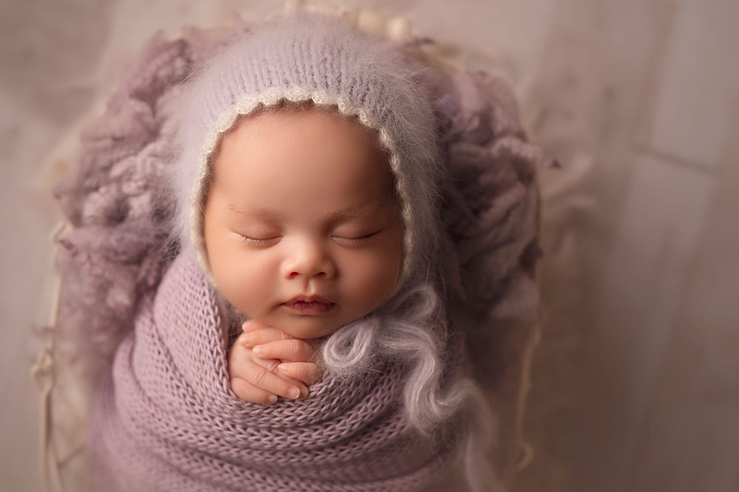 Baby girl in purple bonnet by Annie Whitaker Photography