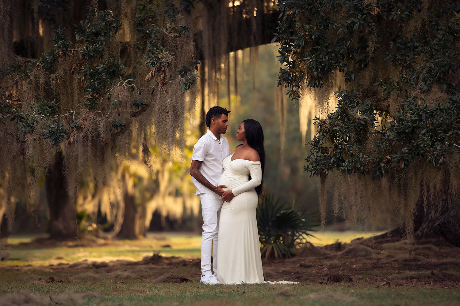 husband and wife expecting baby under oak tree by Annie Whitaker Photography