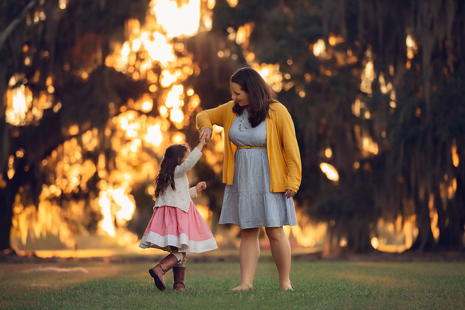 mother and daughter twirling at sunset by Annie Whitaker Photography
