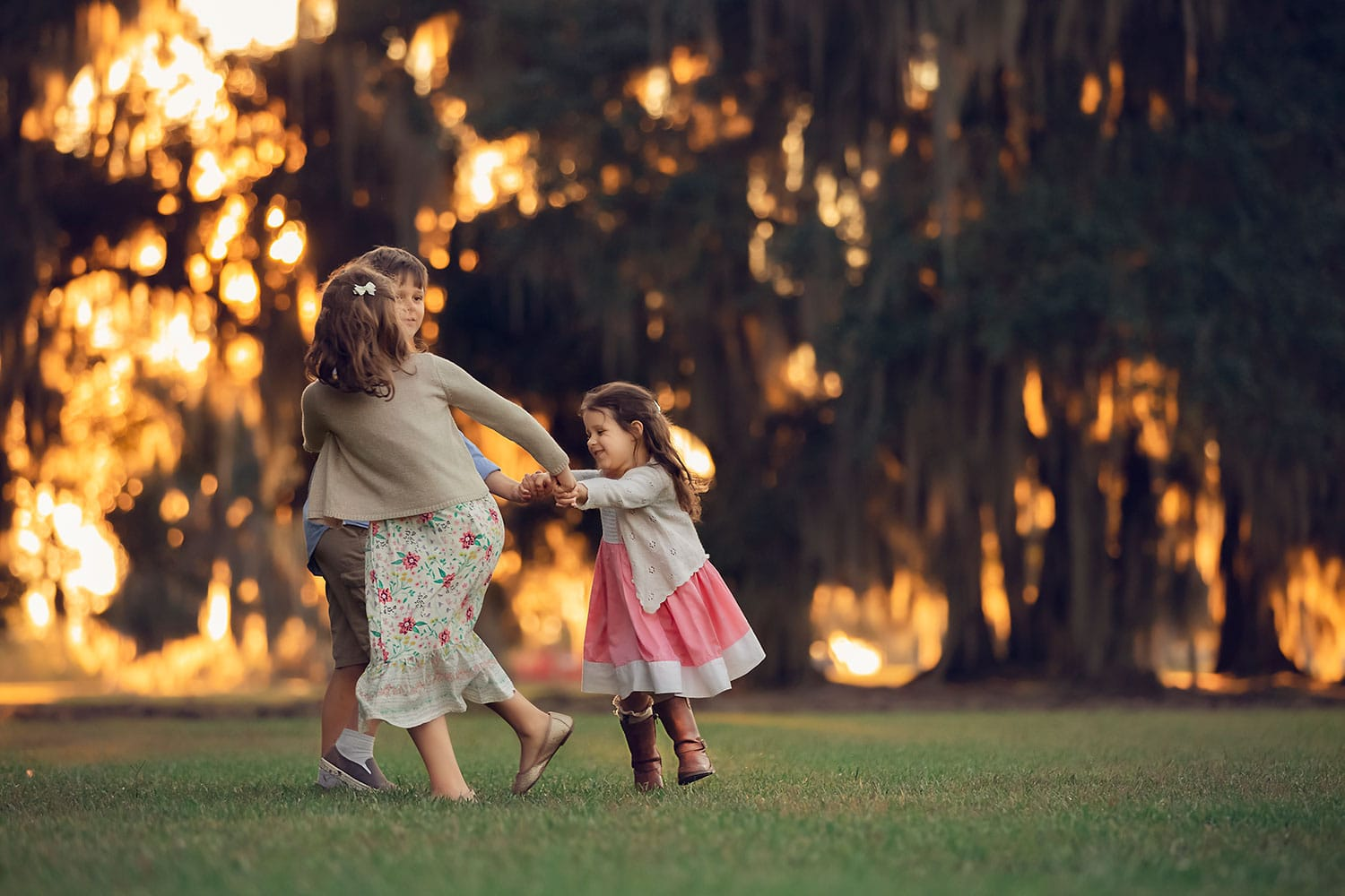 children playing ring around the Rosie at sunset by Annie Whitaker Photography