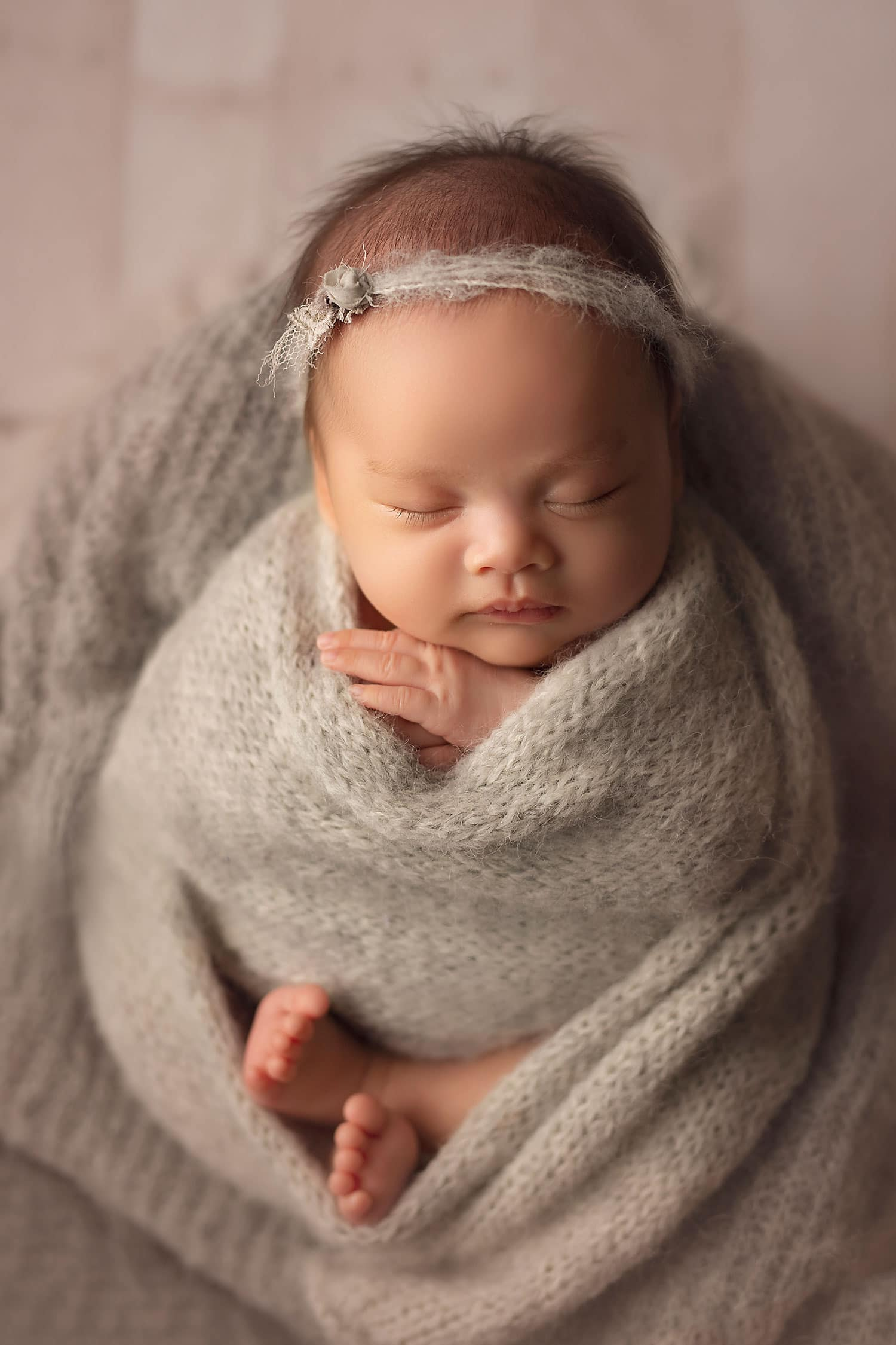 Newborn baby in grey wrap by Annie Whitaker Photography