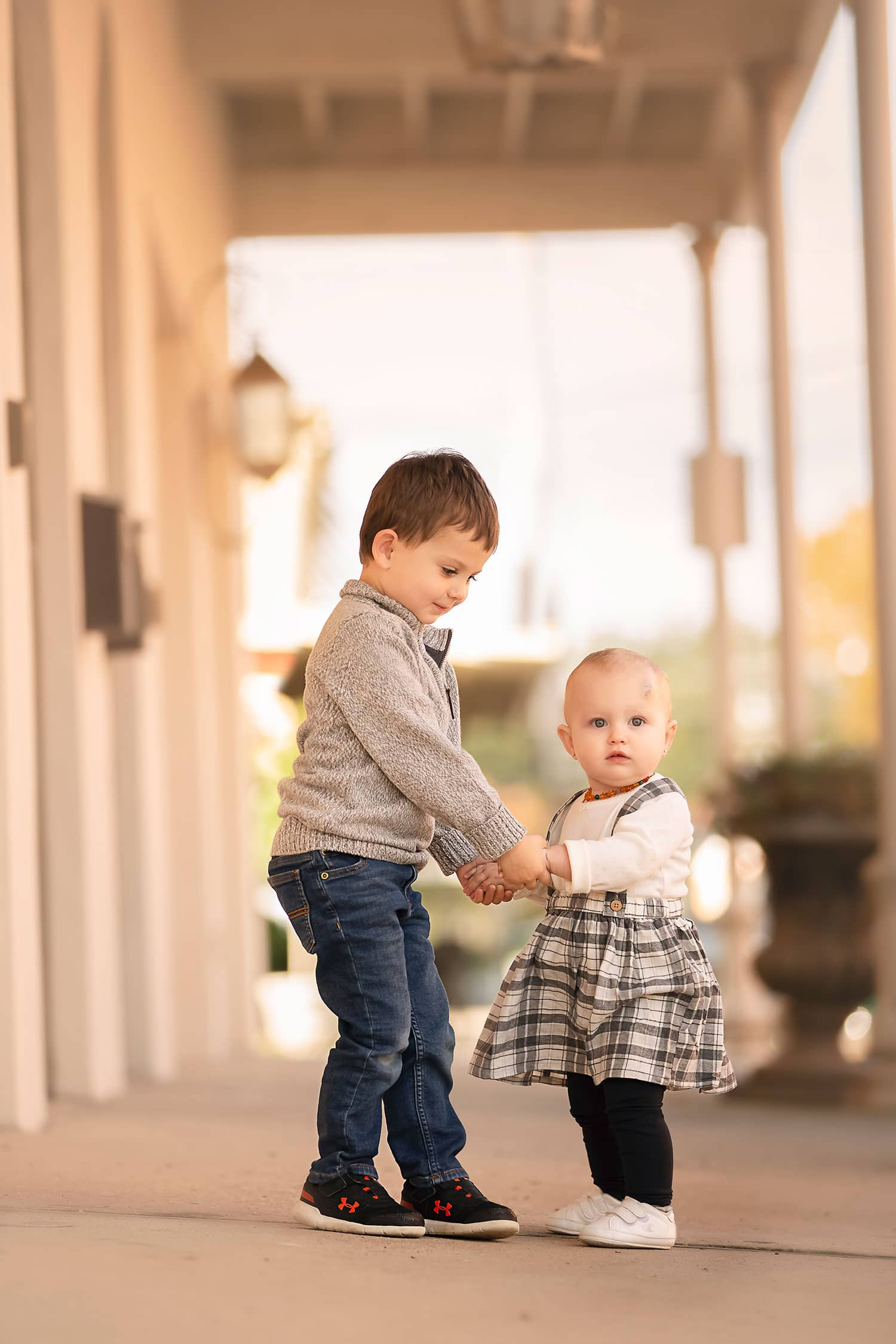 big brother holding little sister's hand by Annie Whitaker Photography