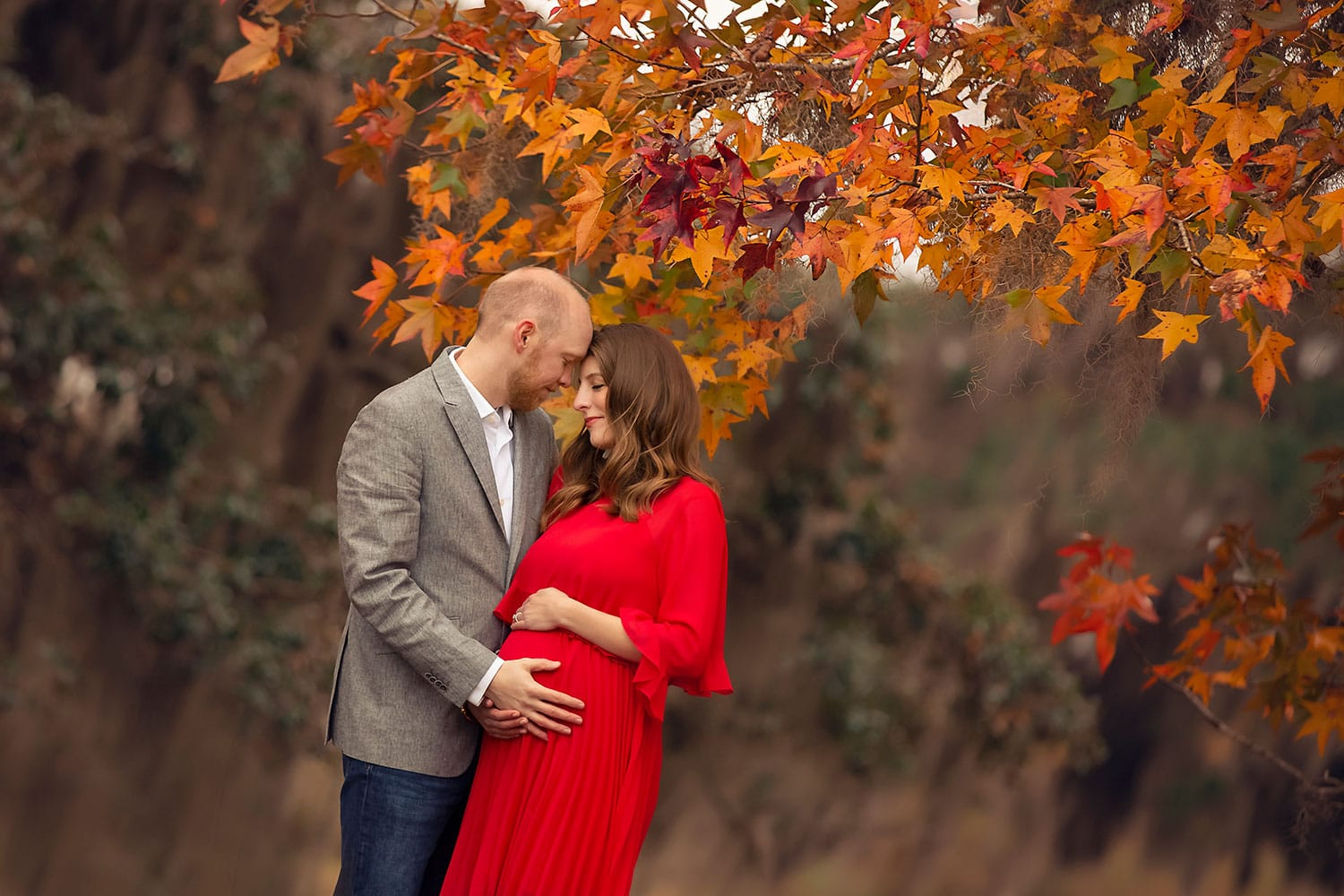 Stunning image of expecting couple by fall foliage by Annie Whitaker