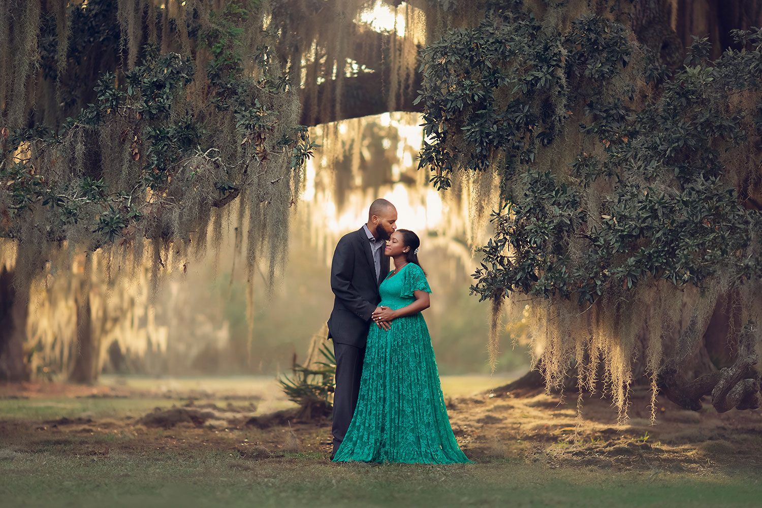 Expecting couple stand-in under the oak trees at sunset by Annie Whitaker Photography