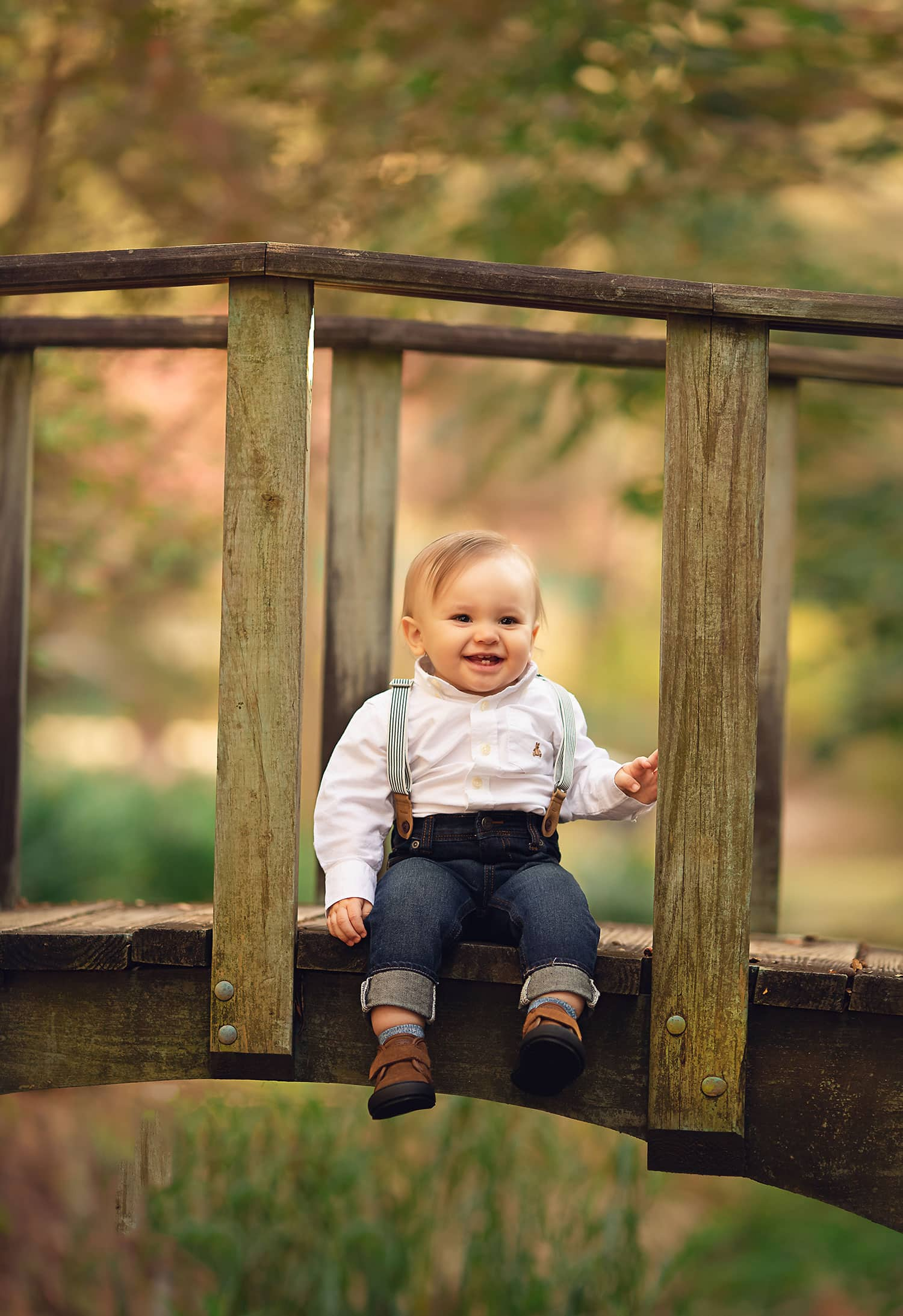 one year old boy smiling on bridge in Mandeville LA