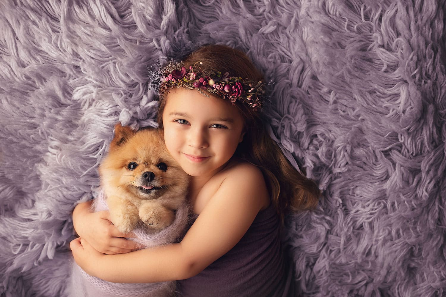 preschooler with puppy on purple flokati