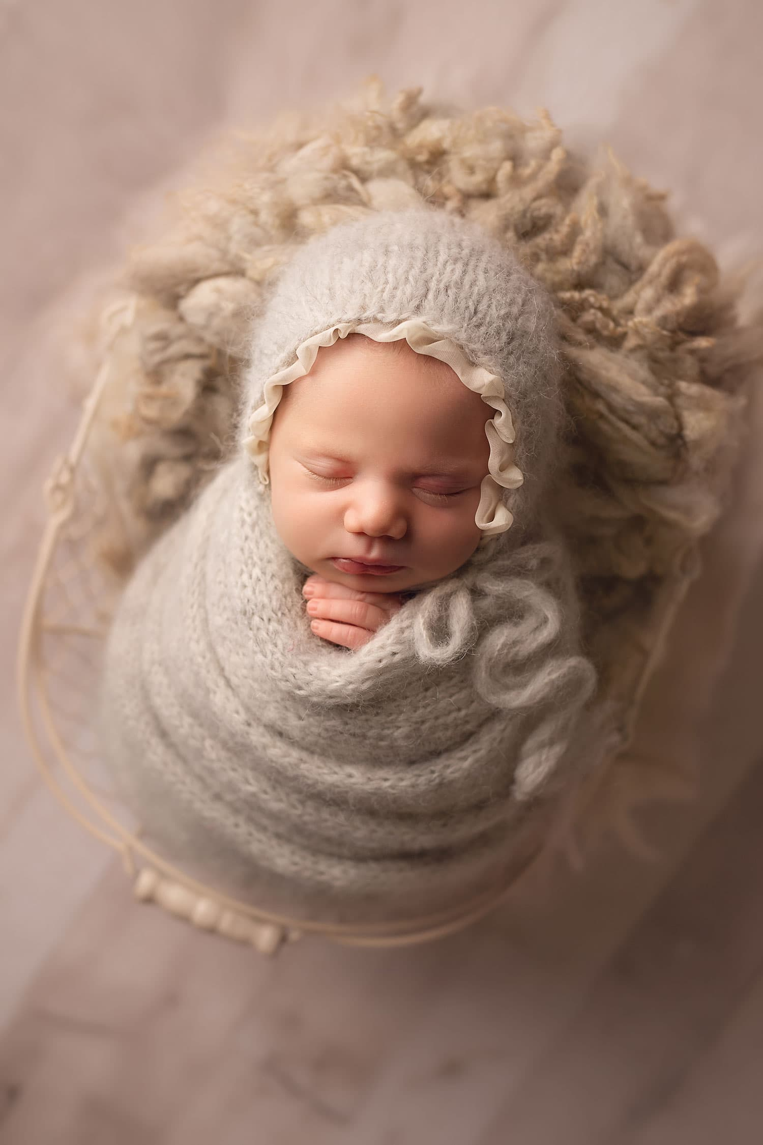 newborn baby girl in gray wrap and bonnet