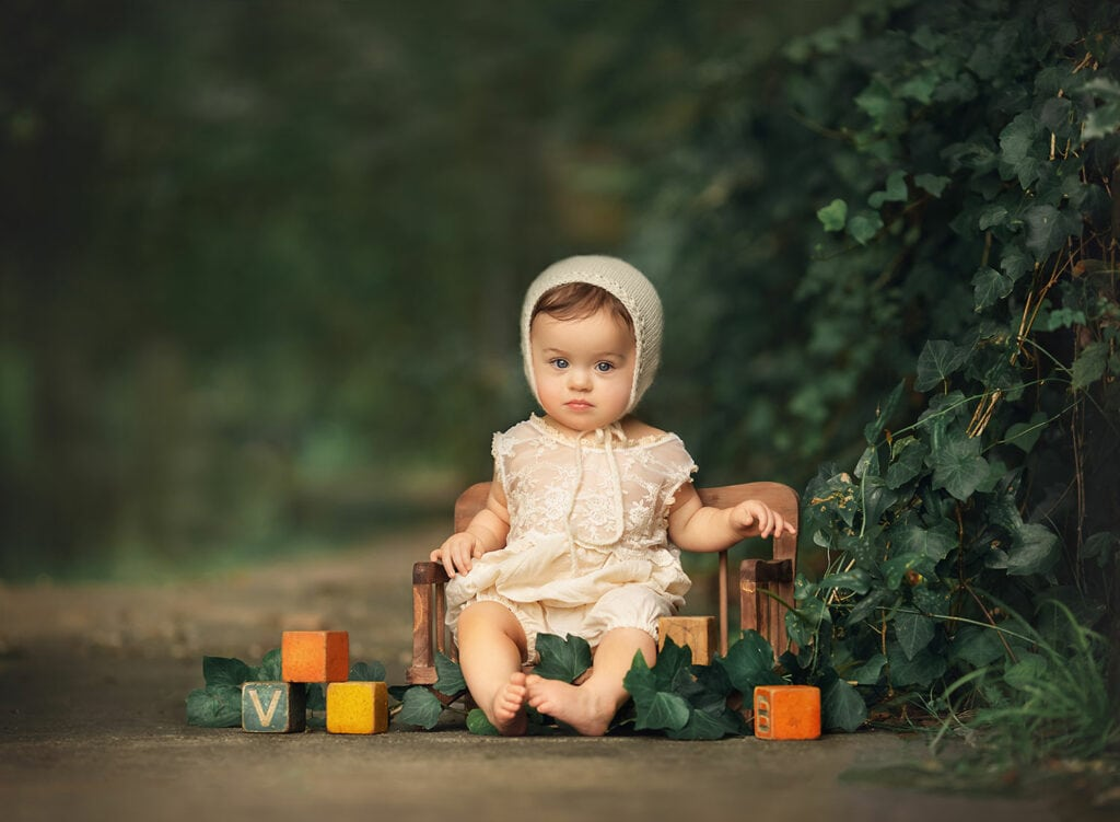 one year old girl in cream bonnet with blocks