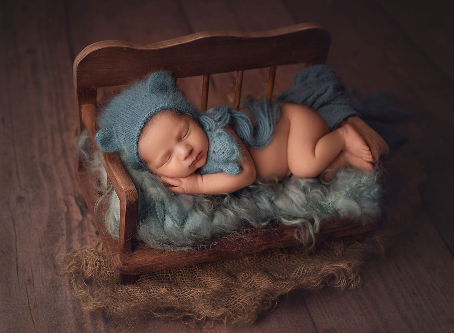 newborn boy in blue bear bonnet holding baby bear in tiny bed