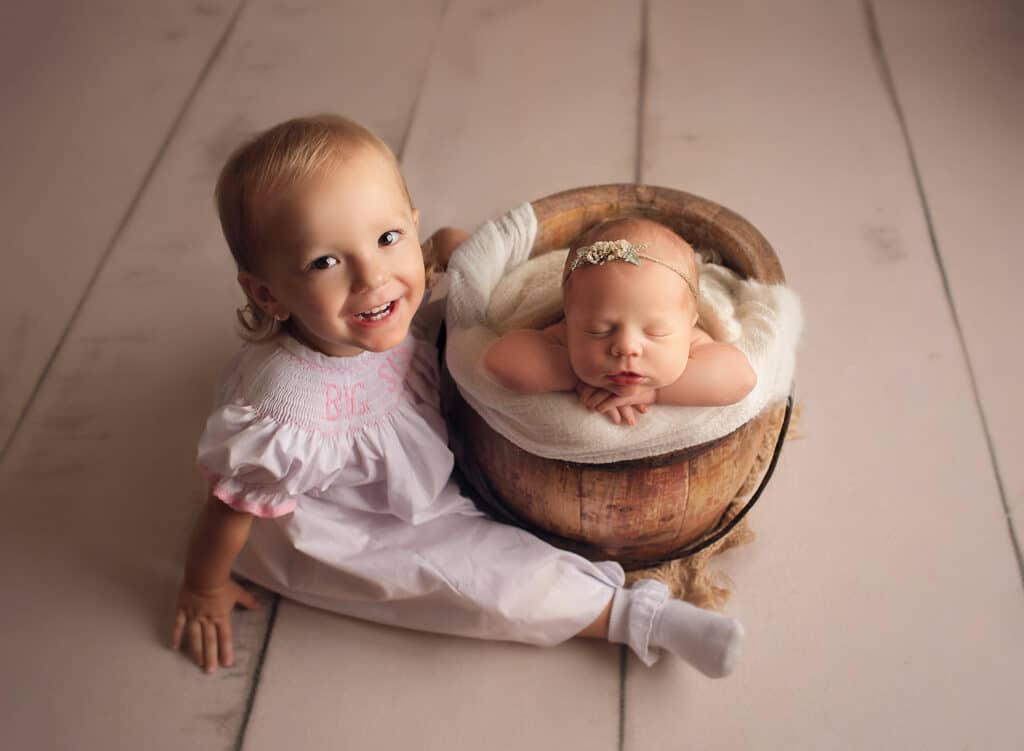 one year old and newborn in bucket pose