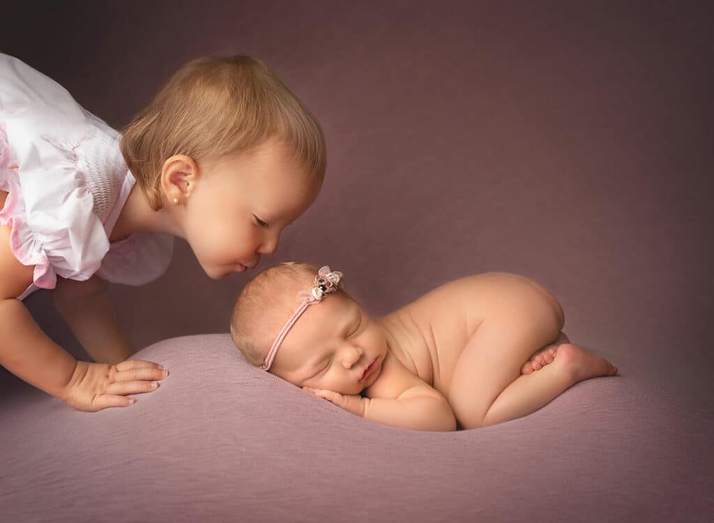 big sister kissing newborn baby