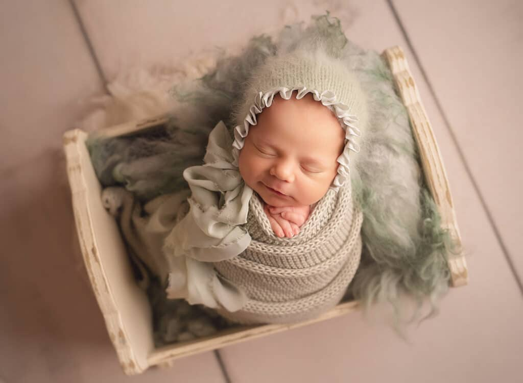 newborn girl in sage set up