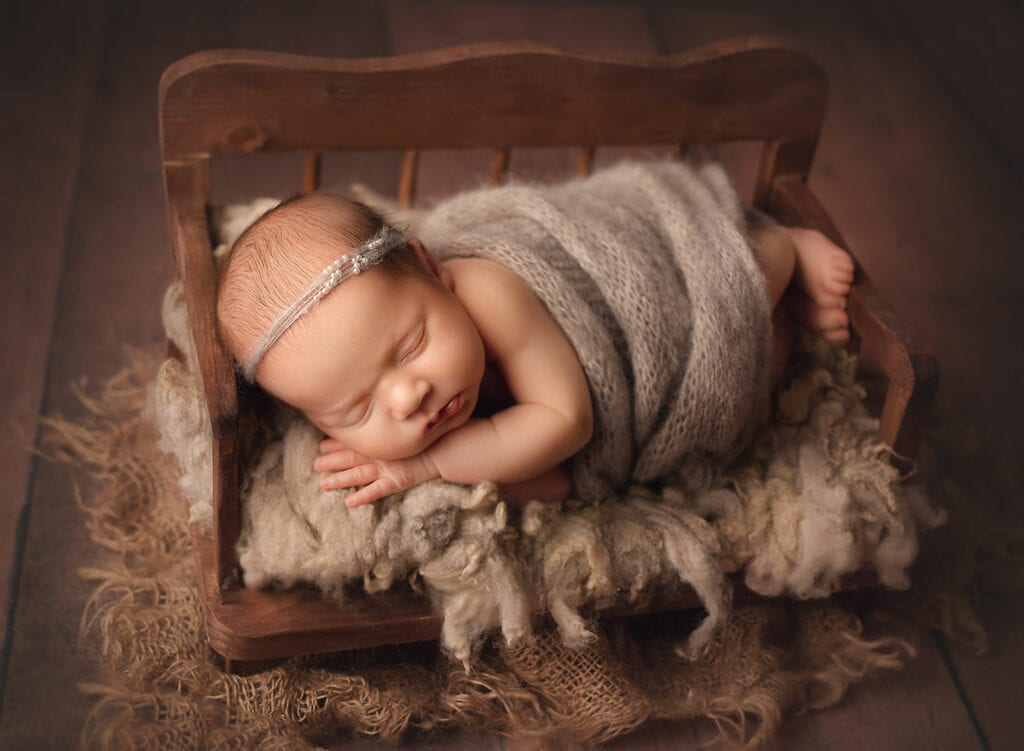 newborn girl in little bed