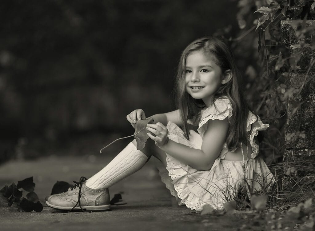 black and white photo of 5 year old girl holding leaf