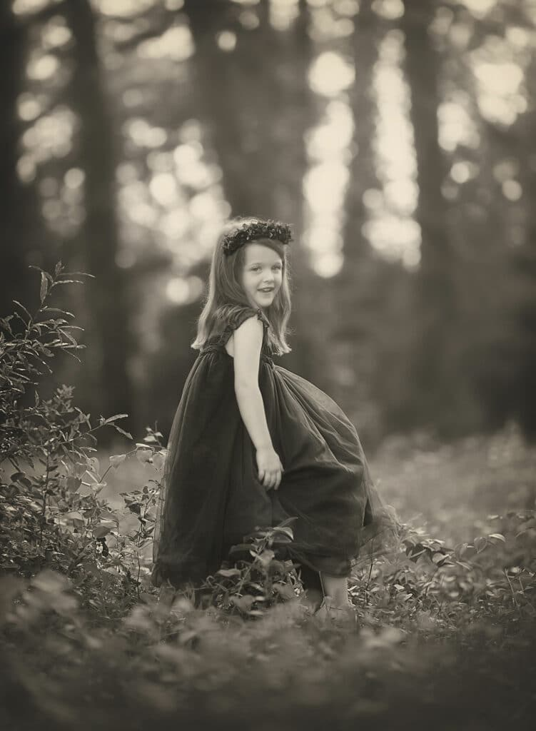 black and white photo of girl in forest