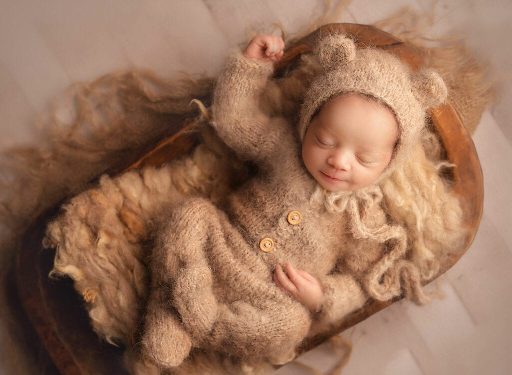 baby relaxed in knit outfit and bear bonnet