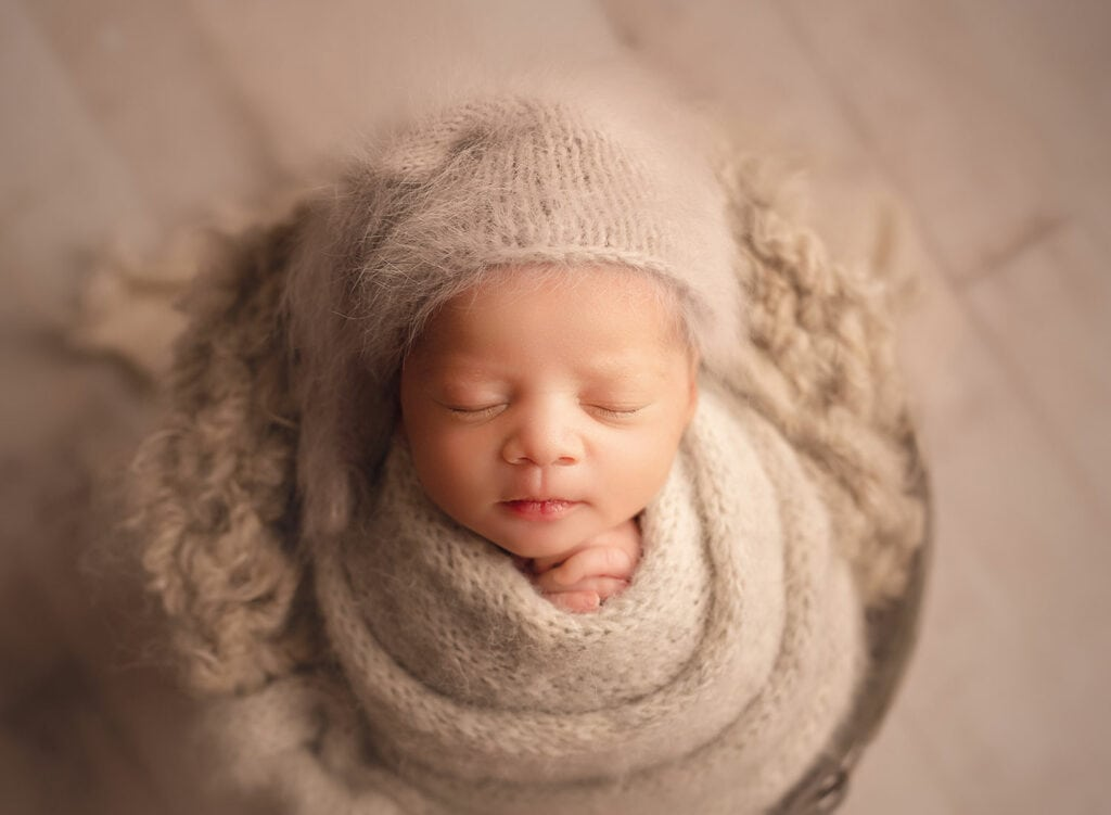 newborn baby in gray wrap and sleepy hat