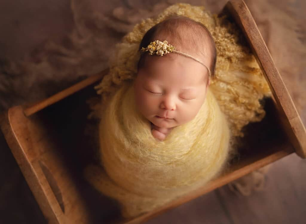 newborn girl in yellow set up
