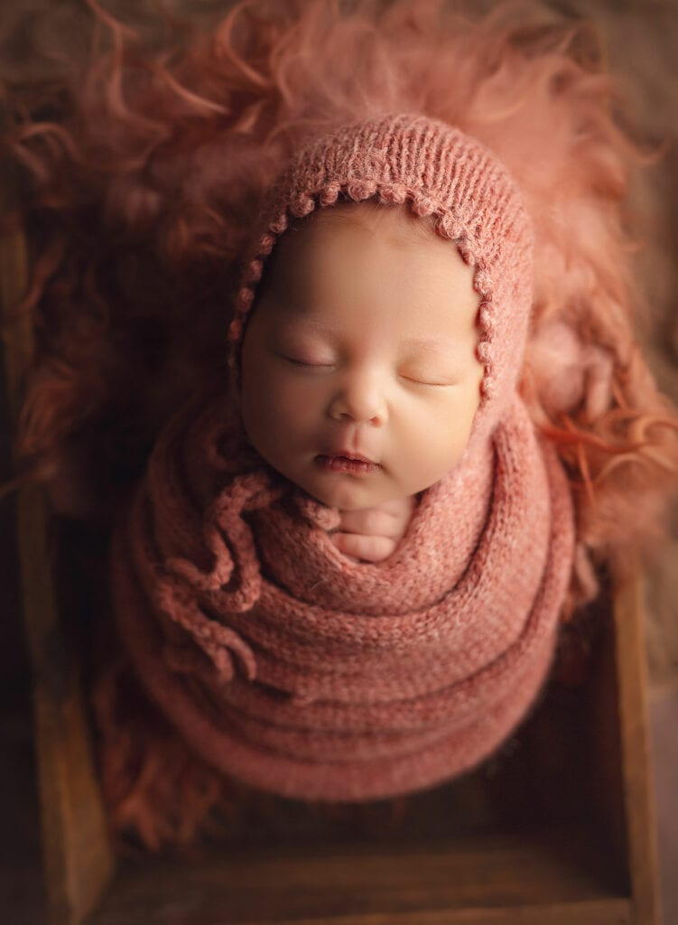 newborn girl in orange wrap and bonnet