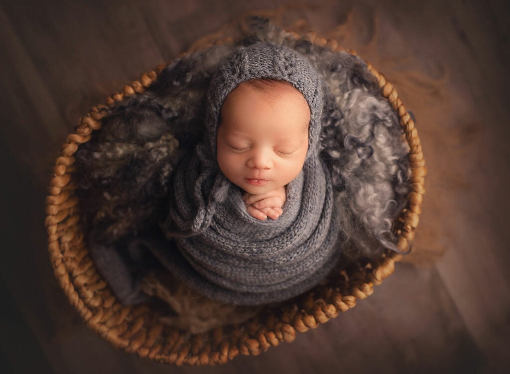 newborn boy in blue wrap and basket