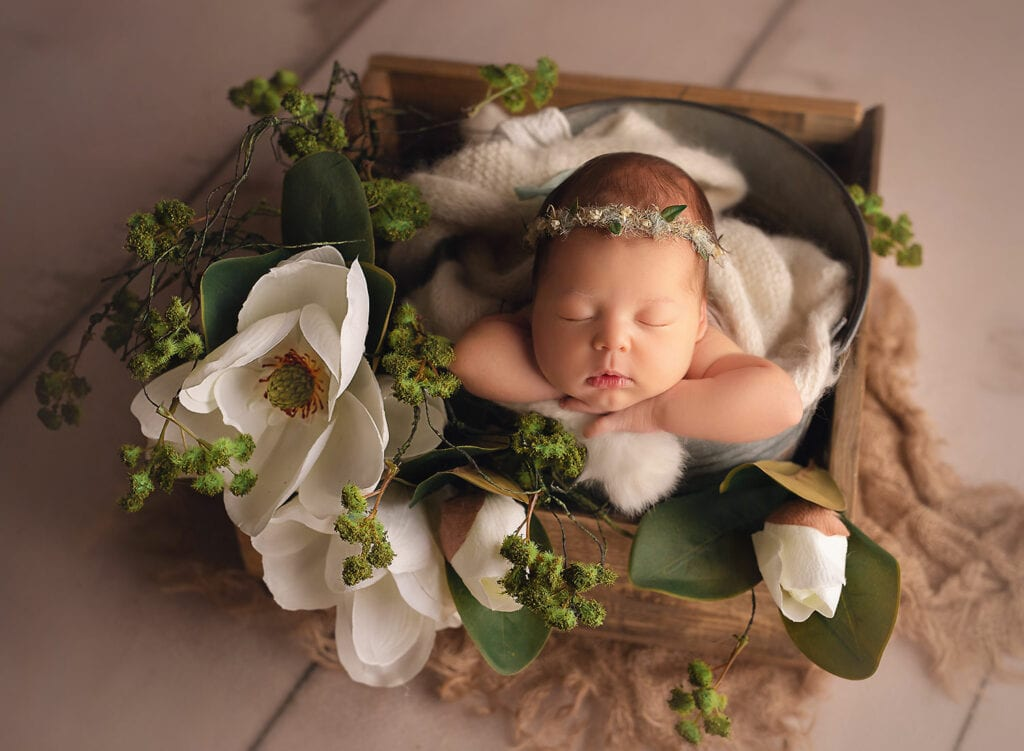 newborn with magnolia flowers
