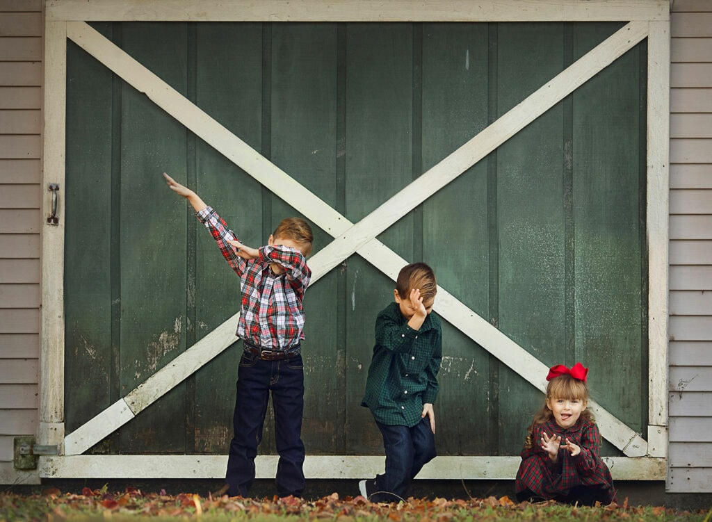 three kids playing in front of barn
