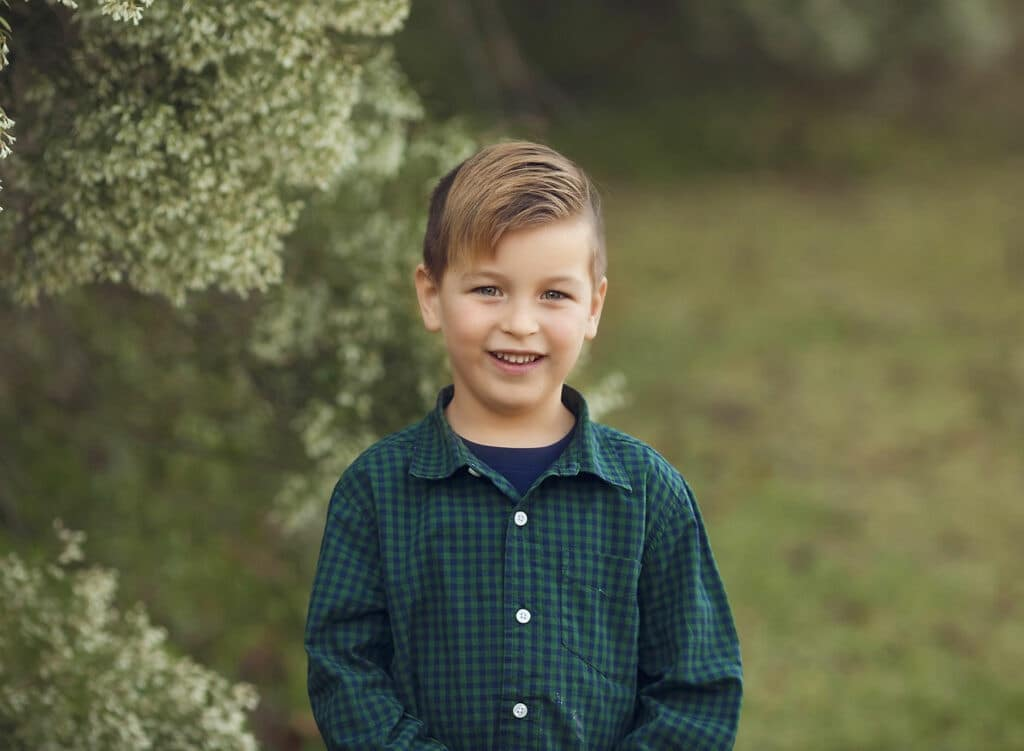 boy in green shirt by white flowers