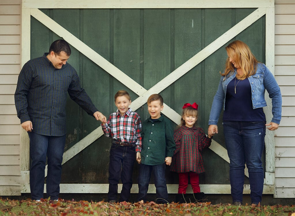 family of five in front of green barn door